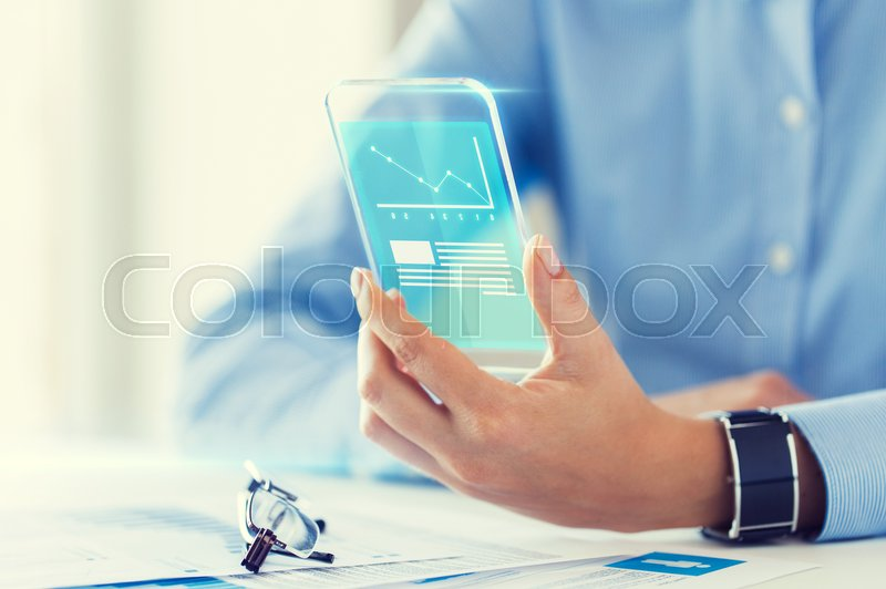 Stock image of 'business, technology and people concept - close up of woman hand holding transparent smartphone with chart on screen at office'