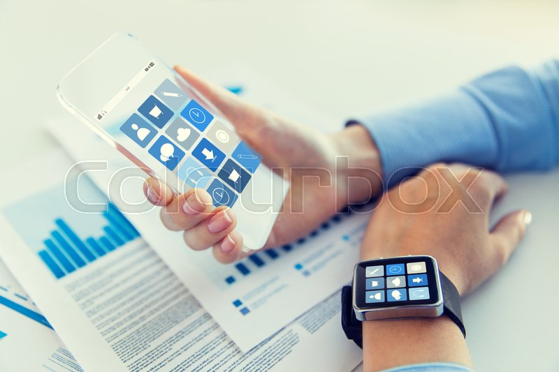 Stock image of 'business, technology and people concept - close up of woman hand holding transparent smartphone and smartwatch with application icons on screen at office'