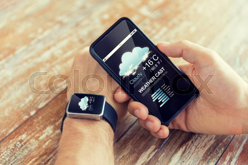 Stock image of 'technology, application, weather forecast and people concept - close up of male hand holding smart phone and wearing watch with cloud icon and air temperature on screen'