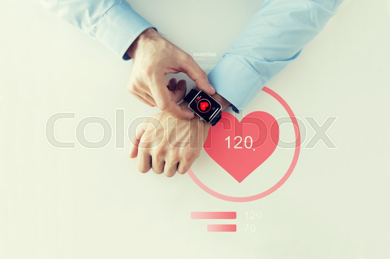 Stock image of 'business, technology, health care, application and people concept - close up of male hands setting smart watch with red heart icon screen'