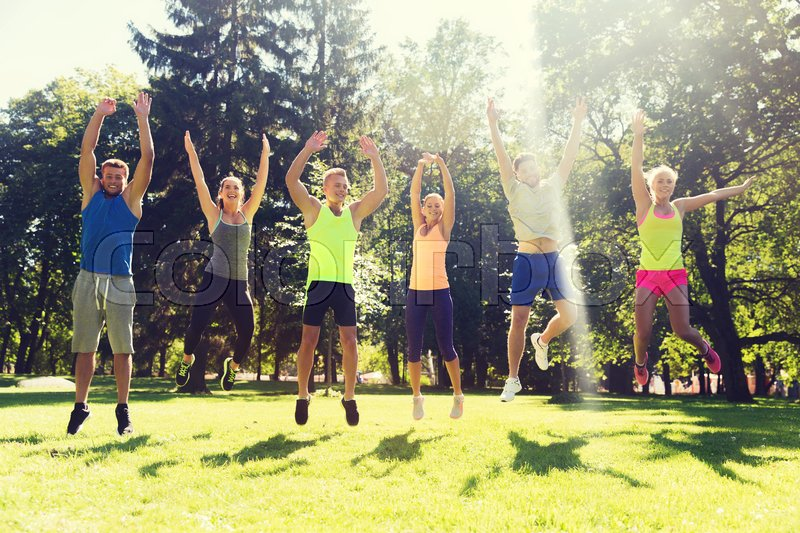 Stock image of 'fitness, sport, friendship and healthy lifestyle concept - group of happy teenage friends or sportsmen jumping high outdoors'