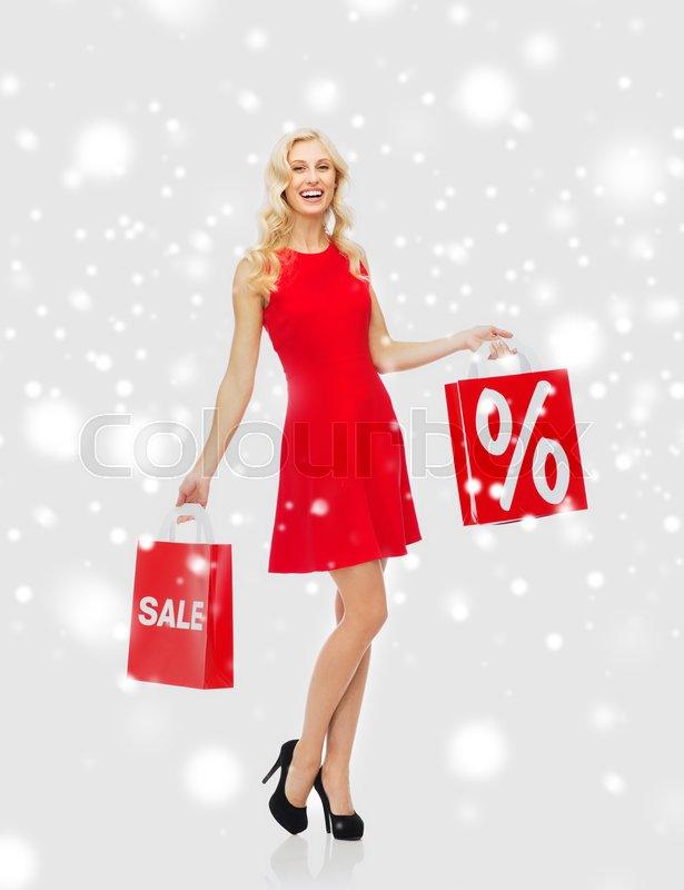 Stock image of 'people, sale, christmas, winter and holidays concept - happy young woman in red dress with shopping bags over snow background'