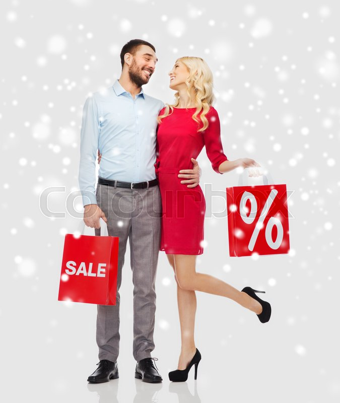 Stock image of 'people, sale, christmas, winter and holidays concept - happy couple with red shopping bags hugging and talking over snow background'