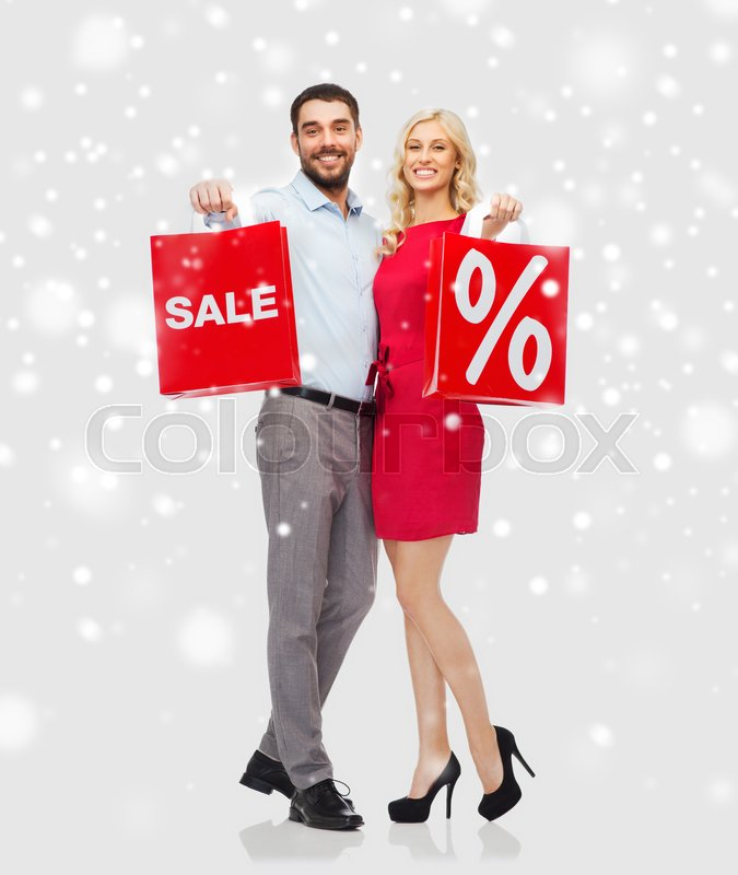 Stock image of 'people, sale, christmas, winter and holidays concept - happy couple with red shopping bags hugging over snow background'
