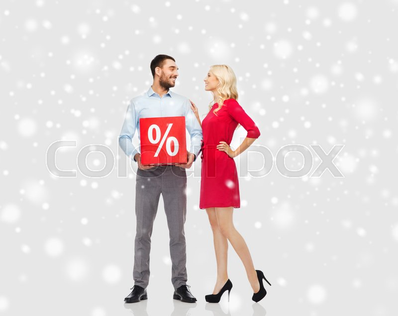Stock image of 'people, sale, christmas, winter shopping and holidays concept - happy couple with red percentage sign over snow background'