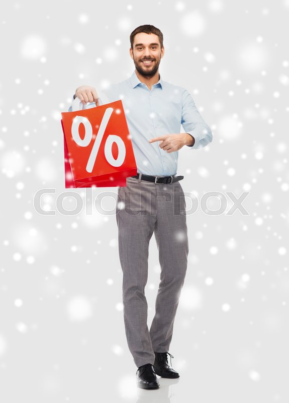 Stock image of 'people, sale, christmas, winter and holidays concept - smiling man holding red shopping bag with percentage sign over snow background'