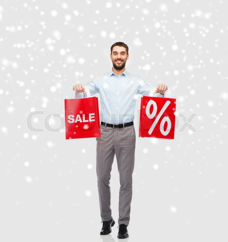 Stock image of 'people, sale, christmas, winter and holidays concept - smiling man holding red shopping bags with percentage sign over snow background'