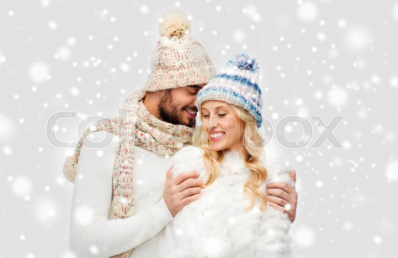 Stock image of 'winter, fashion, couple, christmas and people concept - smiling man and woman in hats and scarf hugging over snow background'