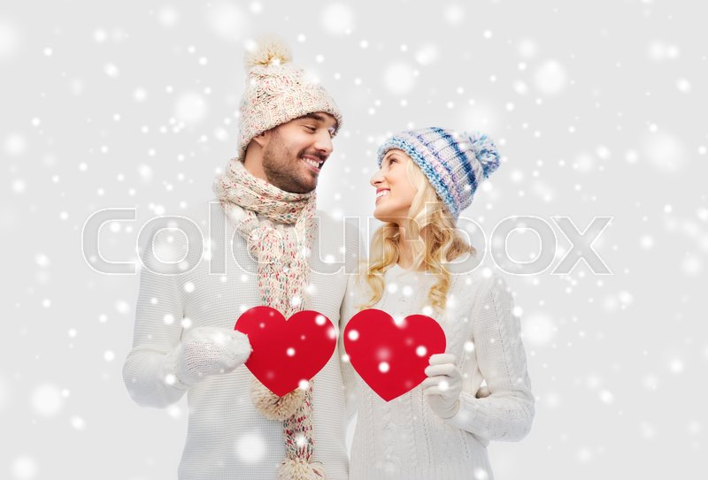 Stock image of 'love, valentines day, couple, christmas and people concept - smiling man and woman in winter hats and scarf holding red paper heart shapes'