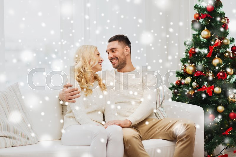 Stock image of 'family, christmas, holidays, love and people concept - happy couple sitting on sofa at home'
