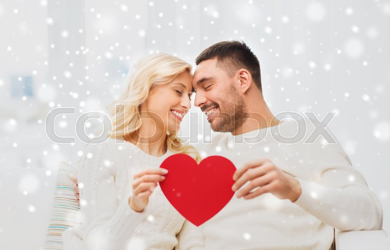 Stock image of 'family, love, valentines day and people concept - happy couple with red heart hugging on sofa at home'