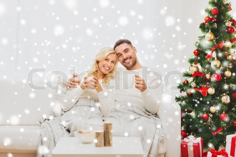 Stock image of 'family, christmas, holidays, love and people concept - happy couple covered with plaid drinking tea and sitting on sofa at home'