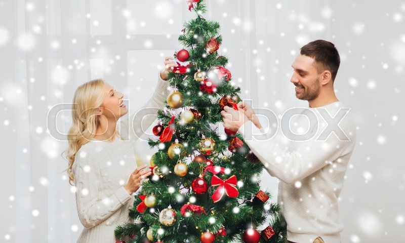 Stock image of 'family, x-mas, winter holidays and people concept - happy couple decorating christmas tree at home'