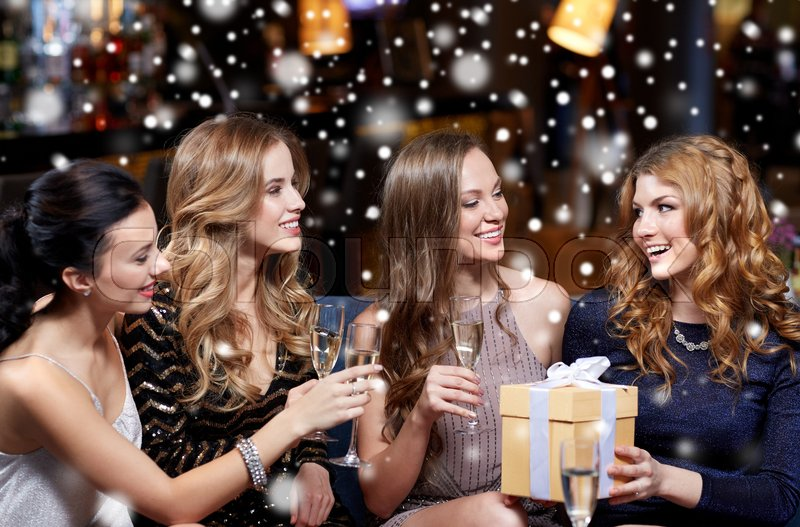 Stock image of 'celebration, friends, new year, christmas and winter holidays concept - happy women with champagne glasses and gift box at bachelorette or birthday party at night club over snow'