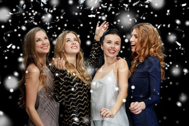Stock image of 'new year party, christmas, winter holidays and people concept - happy young women dancing over black background with snow'