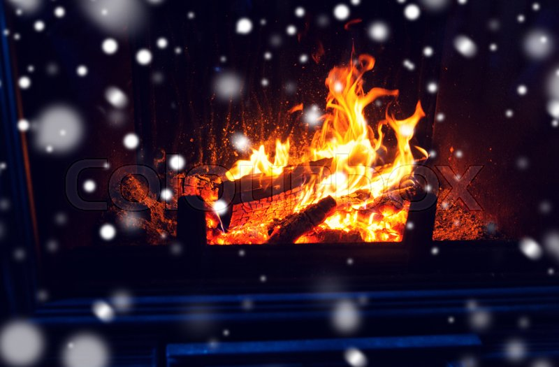 Stock image of 'winter, christmas, warmth, fire and coziness concept - close up of burning fireplace with snow'