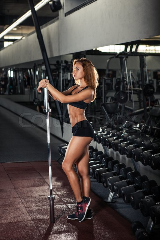 Stock image of 'Attractive young athlete with muscular body. Woman in sportswear posing in gym'