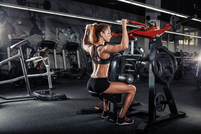 Stock image of 'Muscular fitness woman doing exercises in the gym. Fitness - concept of healthy lifestyle.'