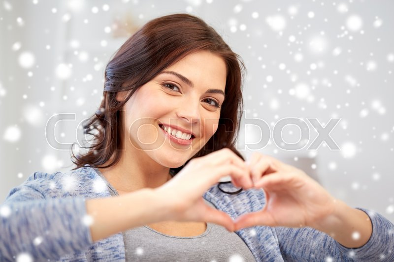 Stock image of 'people, love, valentines day, charity and christmas concept - happy young woman showing heart with hands at home over snow'