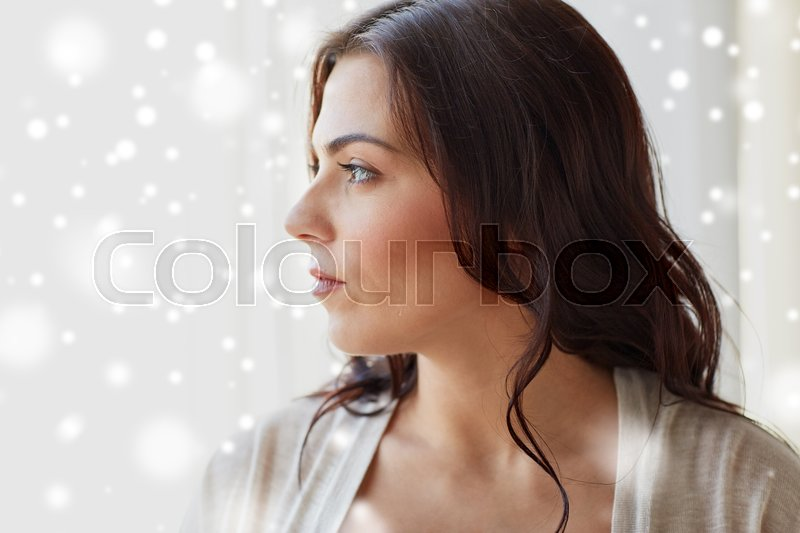 Stock image of 'people, christmas and winter concept - close up of young woman looking through window at home over snow'