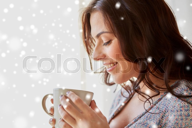 Stock image of 'people, drinks, christmas and winter concept - close up of happy young woman with cup of tea or coffee at home over snow'