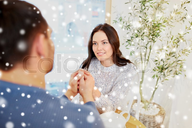 Stock image of 'people, love, romance and dating concept - happy couple drinking tea and holding hands at cafe or restaurant'