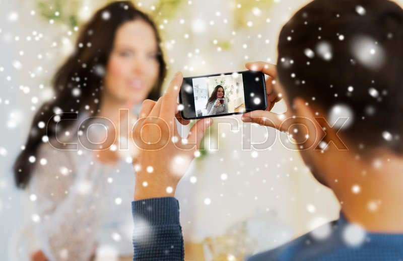 Stock image of 'people, technology and dating concept - close up of man with smartphone taking picture of woman drinking tea at cafe or restaurant'