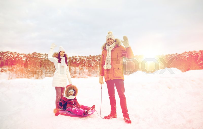 Stock image of 'parenthood, fashion, season, gesture and people concept - happy family with child on sled walking and waving hand in winter outdoors'
