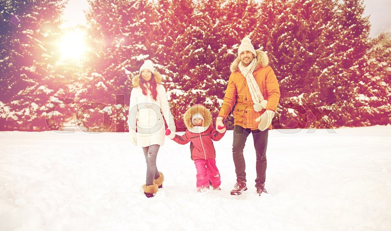 Stock image of 'parenthood, fashion, season and people concept - happy family with child in winter clothes walking outdoors'