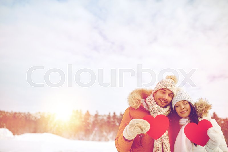 Stock image of 'people, season, love and valentines day concept - happy couple holding blank red hearts over winter landscape'