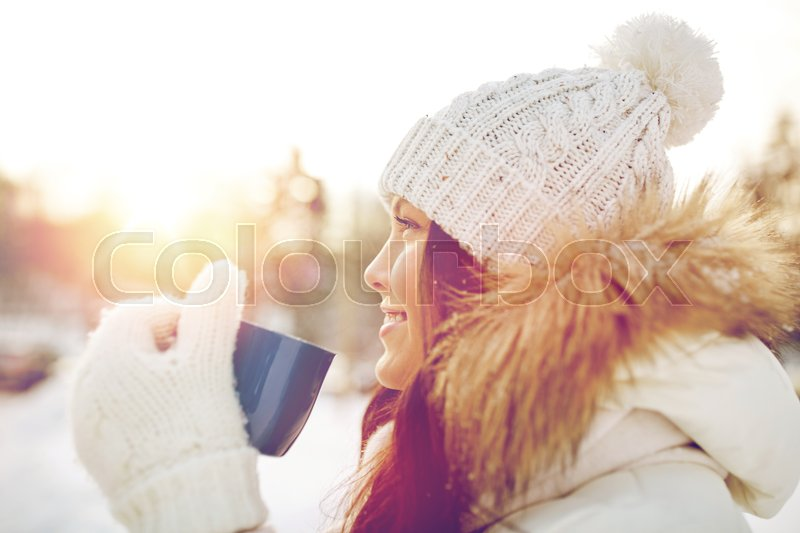 Stock image of 'people, season, drinks and leisure concept - happy young woman with tea cup outdoors in winter'