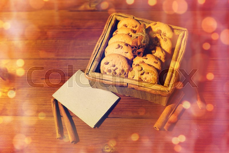 Stock image of 'christmas, baking, culinary, holidays and food concept - close up of oat cookies in wooden box with blank greeting card and cinnamon on table'