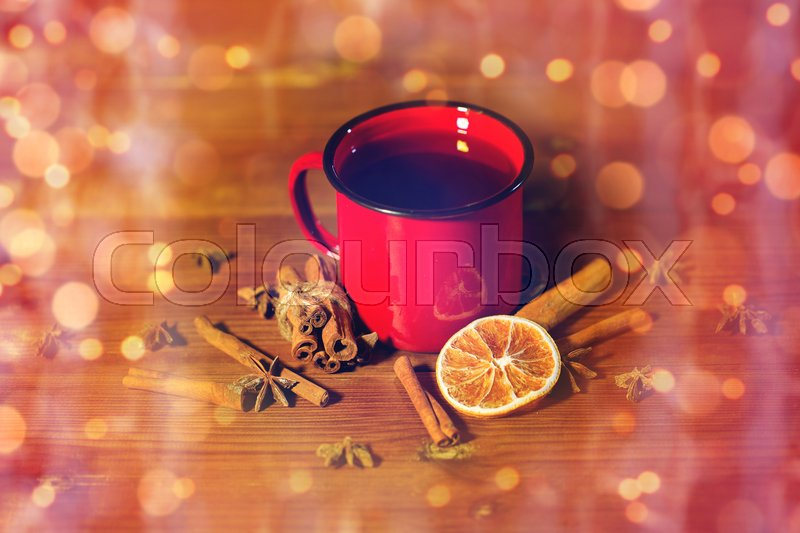 Stock image of 'christmas, holidays, cooking and spice concept - close up of tea cup with cinnamon, anise and dried orange on wooden table from top'