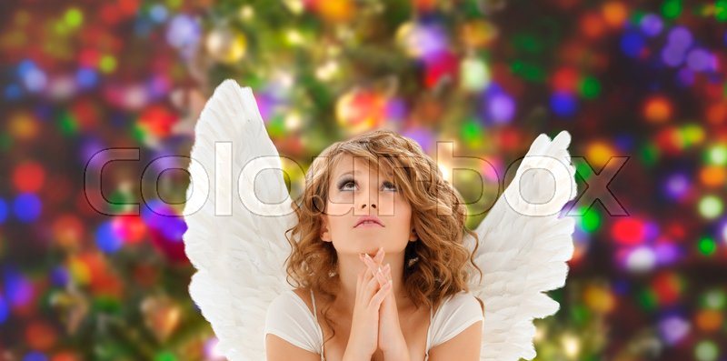 Stock image of 'religion, faith, christmas, holidays and people concept - praying teenage girl or young woman with angel wings over lights background'