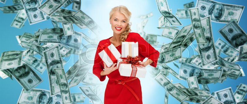 Stock image of 'christmas, people, finance and holidays concept - smiling woman in red dress with many gift boxes over blue background and money rain'