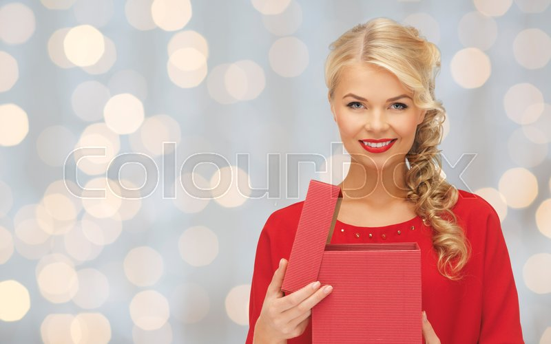 Stock image of 'christmas, holidays, valentines day, birthday and people concept - happy smiling woman in red dress with gift box over lights background'