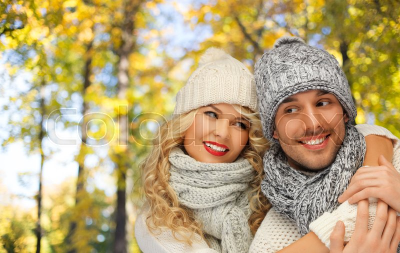 Stock image of 'season, people, love and fashion concept - happy family couple in warm clothes over autumn background'