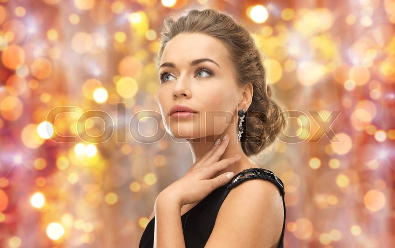 Stock image of 'beauty, luxury, people, holidays and jewelry concept - beautiful woman with gem stone earrings over lights background'