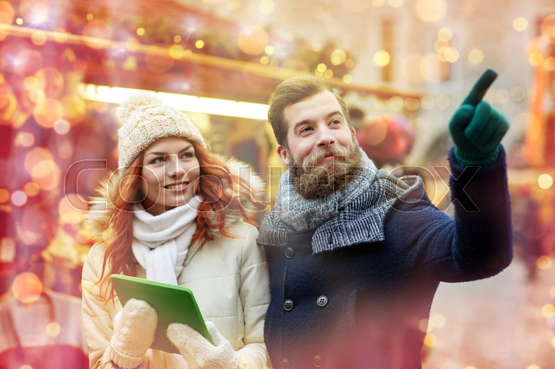Stock image of 'holidays, winter, christmas, technology and people concept - happy couple of tourists in warm clothes with tablet pc computer pointing finger in old town'