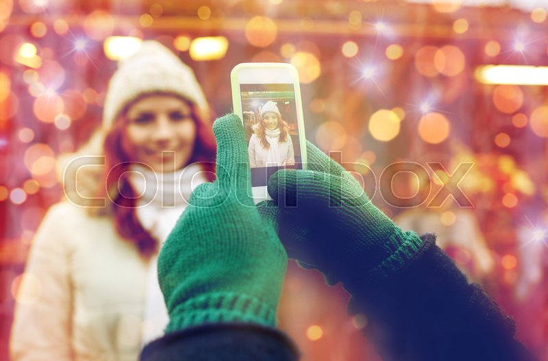 Stock image of 'holidays, winter, christmas, technology and people concept - happy couple of tourists in warm clothes taking picture with smartphone in old town'