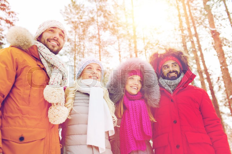 Stock image of 'love, christmas, season, friendship and people concept - group of smiling men and women walking in winter forest'