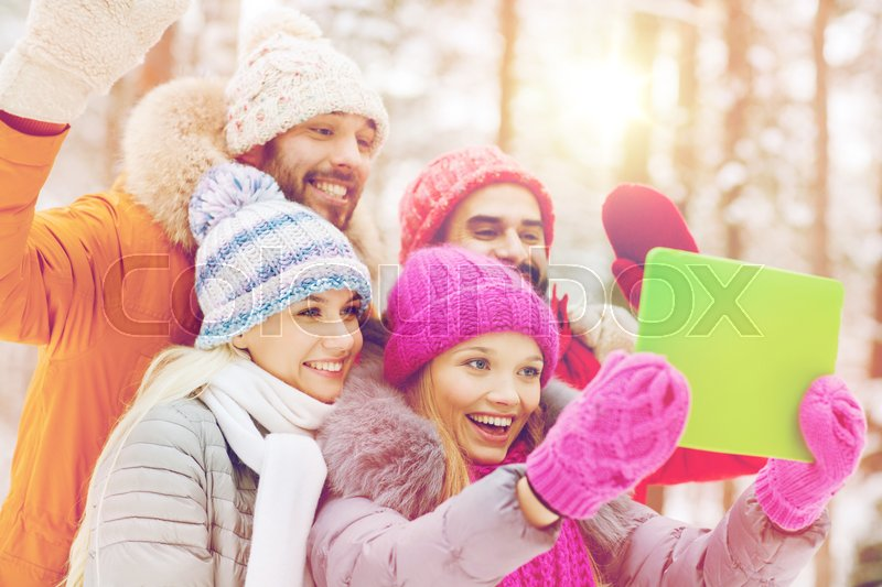 Stock image of 'technology, season, friendship and people concept - group of smiling men and women taking selfie tablet pc computer in winter forest'