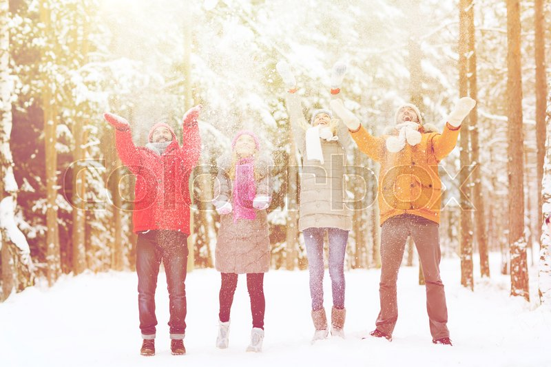 Stock image of 'christmas, season, friendship and people concept - group of happy men and women having fun and playing with snow in winter forest'
