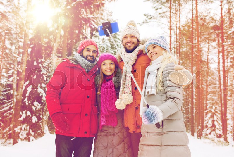 Stock image of 'technology, season, friendship and people concept - group of smiling men and women taking selfie with smartphone and monopod in winter forest'