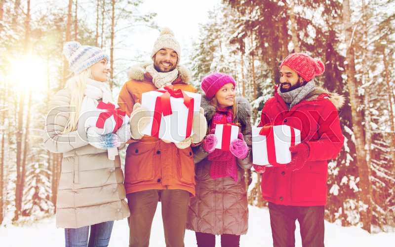Stock image of 'holidays, christmas, season, friendship and people concept - group of smiling friends with gift boxes in winter forest'