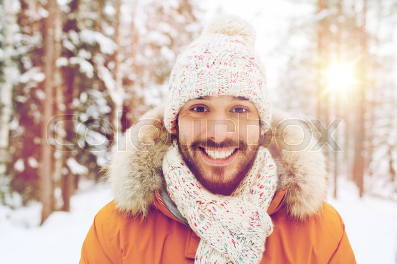Stock image of 'season, christmas and people concept - happy smiling young man in snowy winter forest'