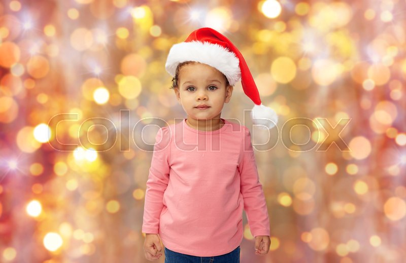 Stock image of 'childhood, christmas, holidays and people concept - beautiful little african american baby girl in santa hat over lights background'