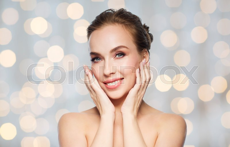 Stock image of 'beauty, people and health concept - beautiful young woman touching her face over holidays lights background'