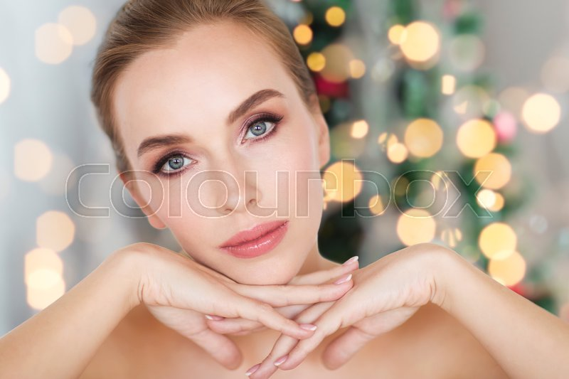 Stock image of 'beauty, people, holidays and bodycare concept -beautiful young woman face and hands over christmas tree lights background'