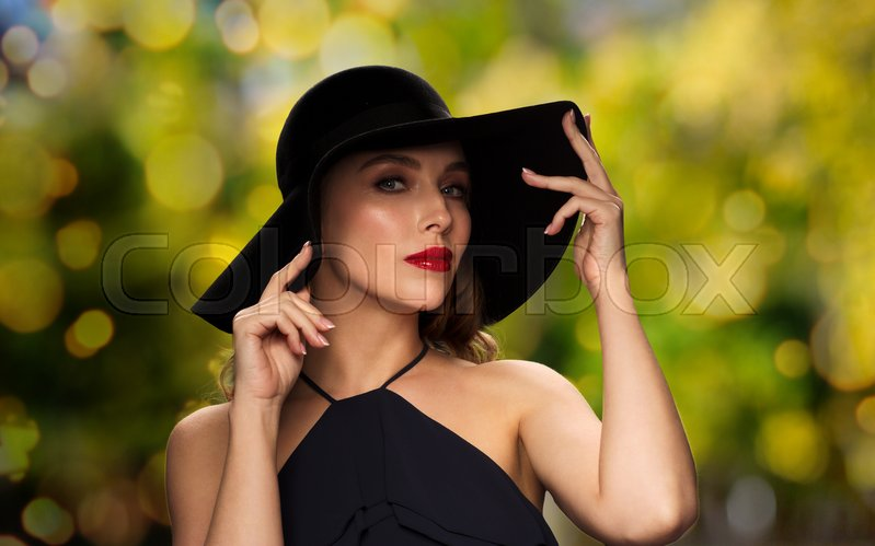 Stock image of 'people, luxury, holidays and fashion concept - beautiful woman in black hat over green lights background'